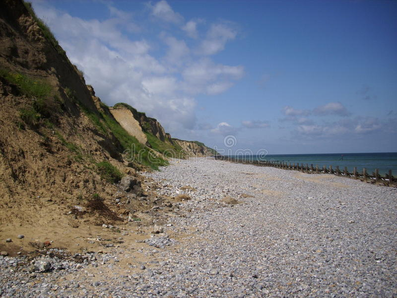 Beach, breakwaters, cliffs and sea. Shingle and sand beach with calm sea and breakwaters (groynes). Lovely blue sky and sea is blue too. Cliffs to one royalty free stock image