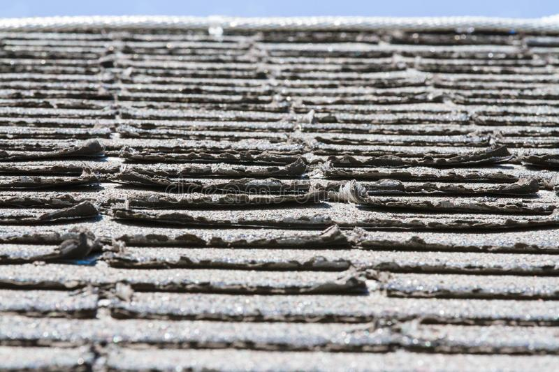Worn-out asphalt shingles on a roof. Shingles needing replacement or repair stock images