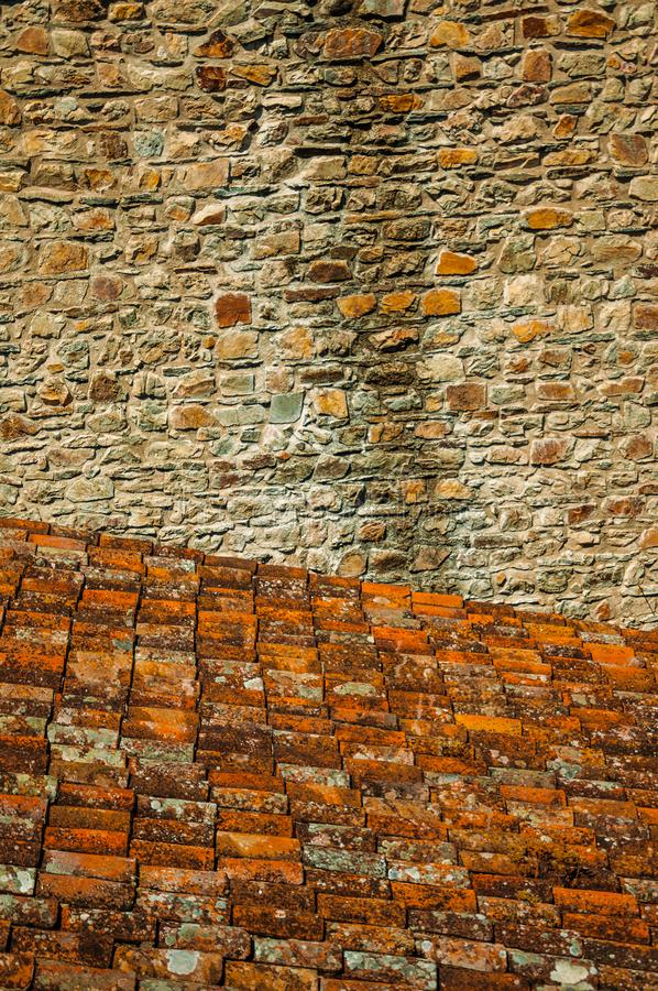 Shingles on roof covered by lichens and stone wall royalty free stock image