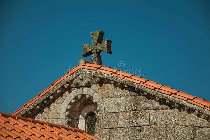 Shingles on roof of medieval Chapel and stone cross stock photography