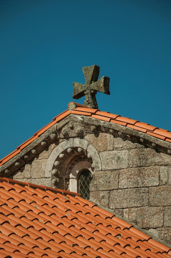 Shingles on roof of medieval chapel and stone cross stock image