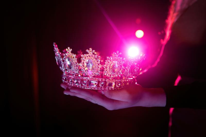Shining crown in the hands. Precious shining crown in the hands of the winner of the beauty contest. Behind the crown is a spotlight that creates a beautiful royalty free stock image