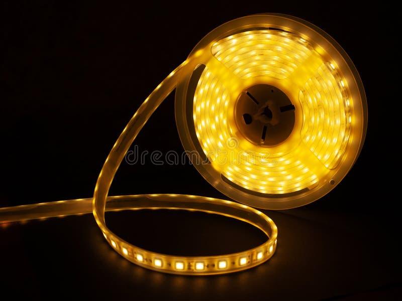 Shining diode strip. LED lights tape closeup.current LEDs-technologies. Shining diode strip. LED lights tape closeup on a black background.current LEDs stock photo