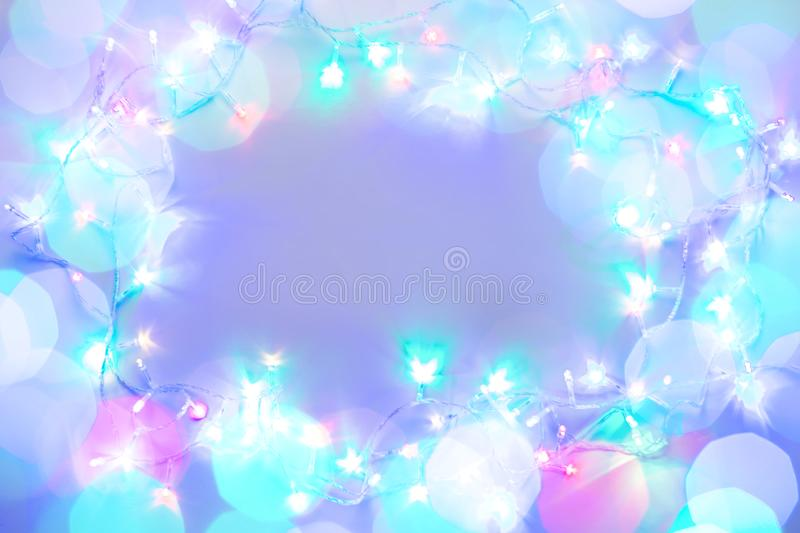 Shining festive multicolor christmas lights frame with copy space, glowing purple garland with colorful bokeh royalty free stock photo