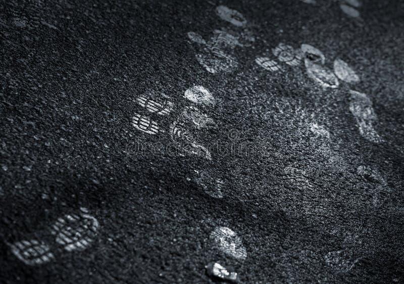Shining footprints on the dark dirty road royalty free stock photos