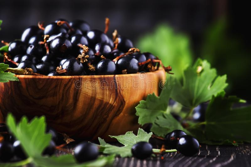 Shining fresh black currants in wooden bowls, summer harvesting, black kitchen table background, place for text, selective focus stock photo