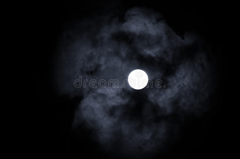 Shining full moon in the night sky and dramatic night clouds -night mysterious landscape in cold tones. Night sky gothic background with full moon beneath the stock image