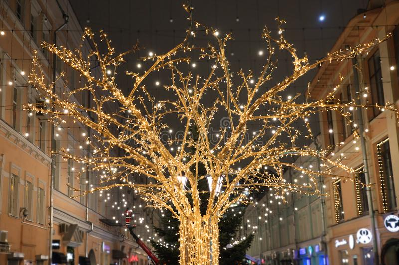 Shining gold tree in led lights on the backdrop of the streets. Of the city stock photo