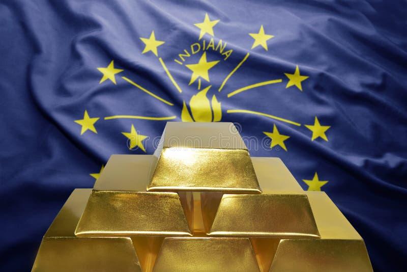 Indiana gold reserves. Shining golden bullions on the indiana flag background royalty free stock photo