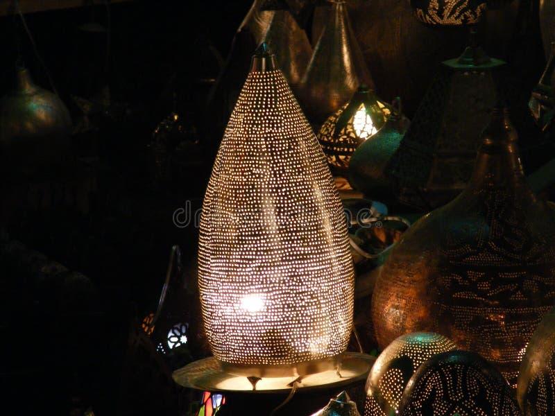 Shining lanterns in khan el khalili souq market with Arabic handwriting on it in egypt cairo. Vendor selling handmade copper oriental lamps ornaments in khan el royalty free stock photo