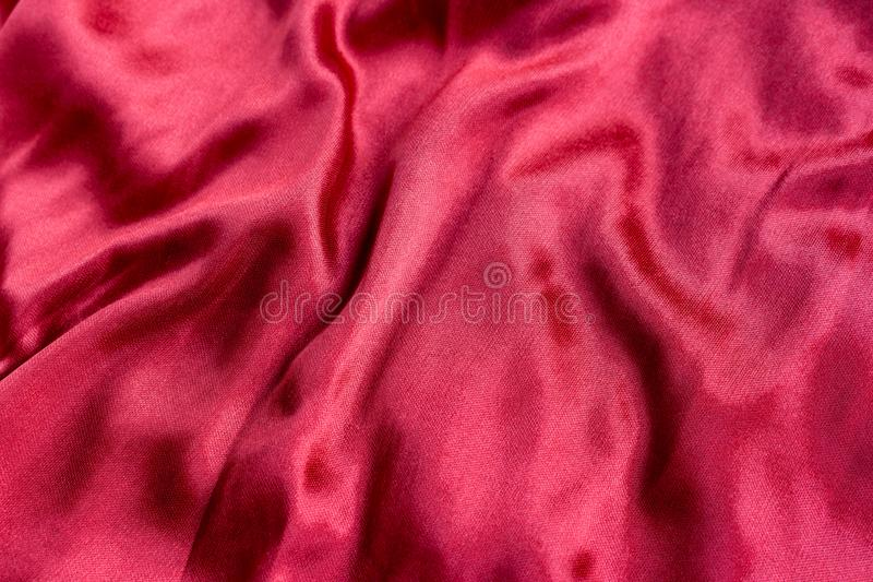 Shining red silk atlas satin fabric with folds, fabric waves. Real fabric background stock images