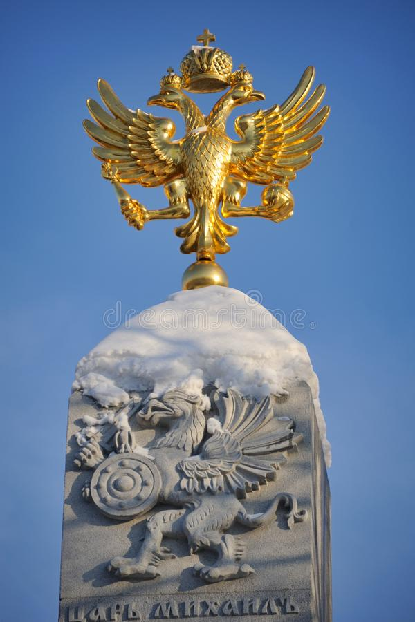 Shining Romanov's Two-Headed Eagle and Griffin in Winter Sunset. MOSCOW, RUSSIA - February 12, 2018 Snow-covered top of the Romanov`s monument with royalty free stock image