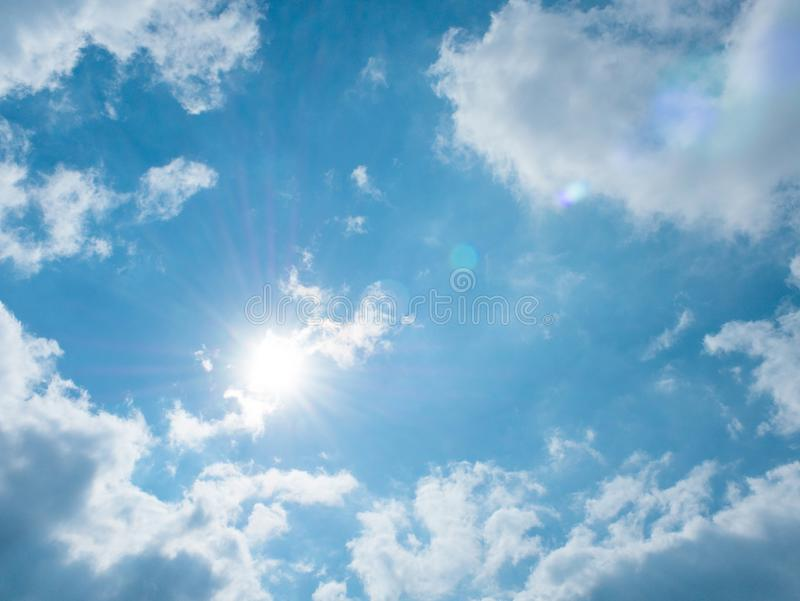 Shining sun and clouds on blue sky background royalty free stock photos