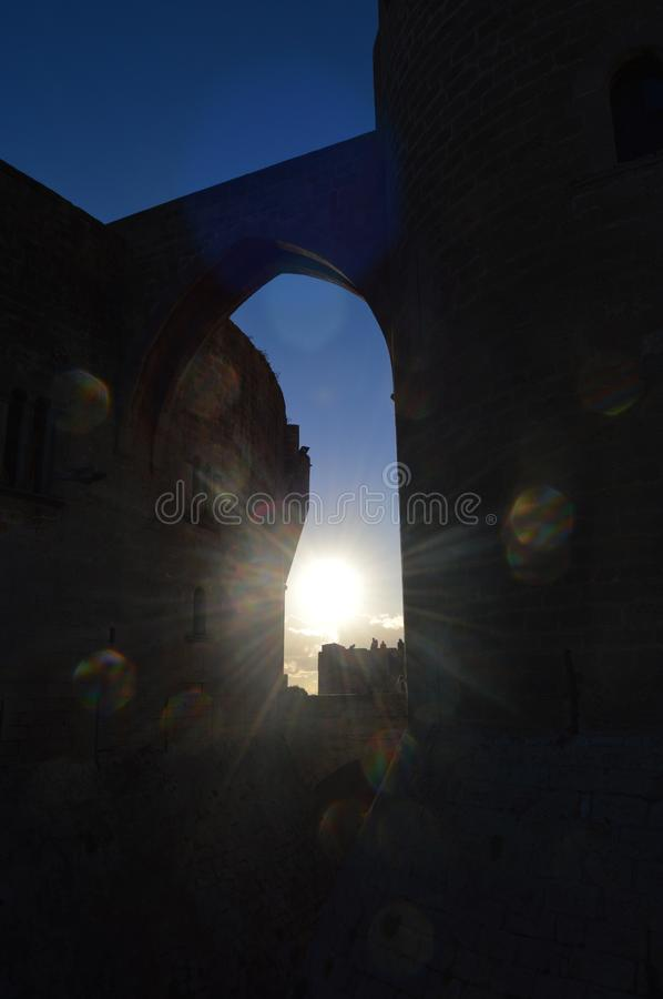 Shining sun at donjon of the Bellver Castle. Sun shining throught the arch of the donjon of the Bellver Castle, a XIII Century Gothic Castell. Bokeh effect royalty free stock photography