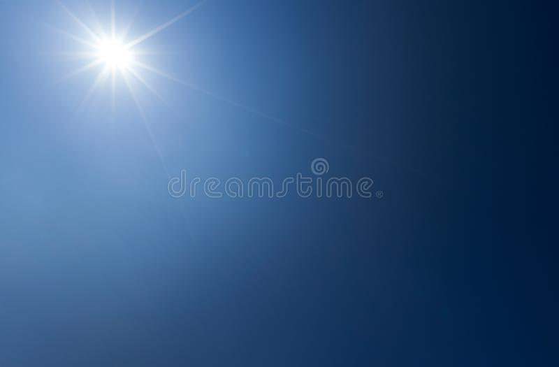 Shining sun with rays and clear gradient blue sky stock images