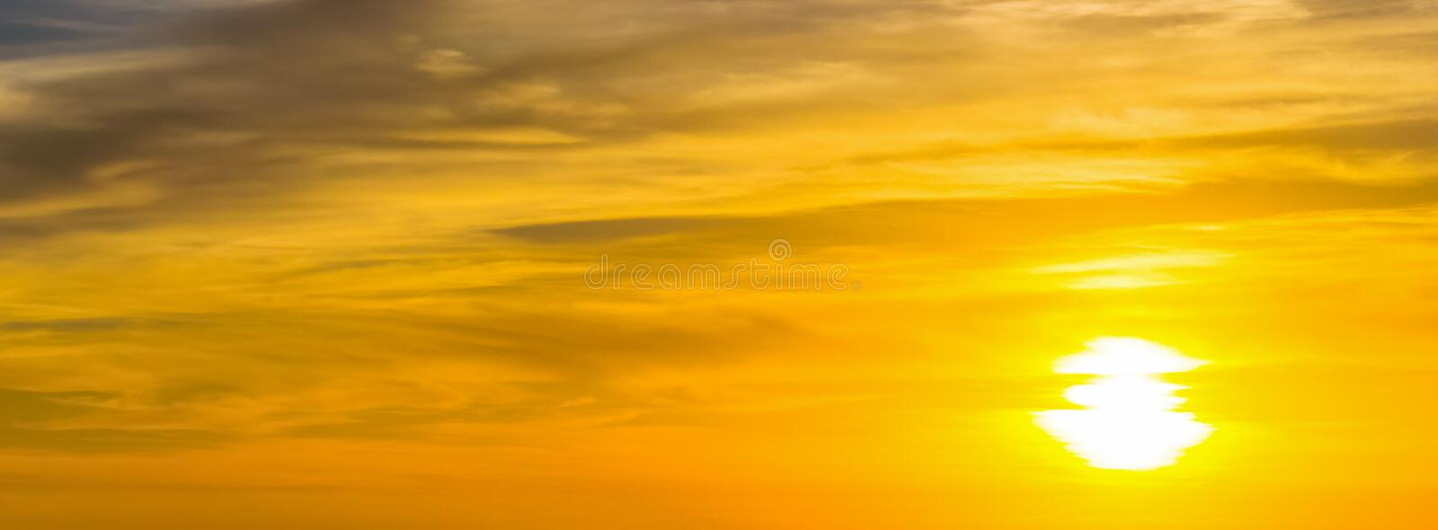 Shining sun at sunset. Blue sky with white, soft clouds stock photo