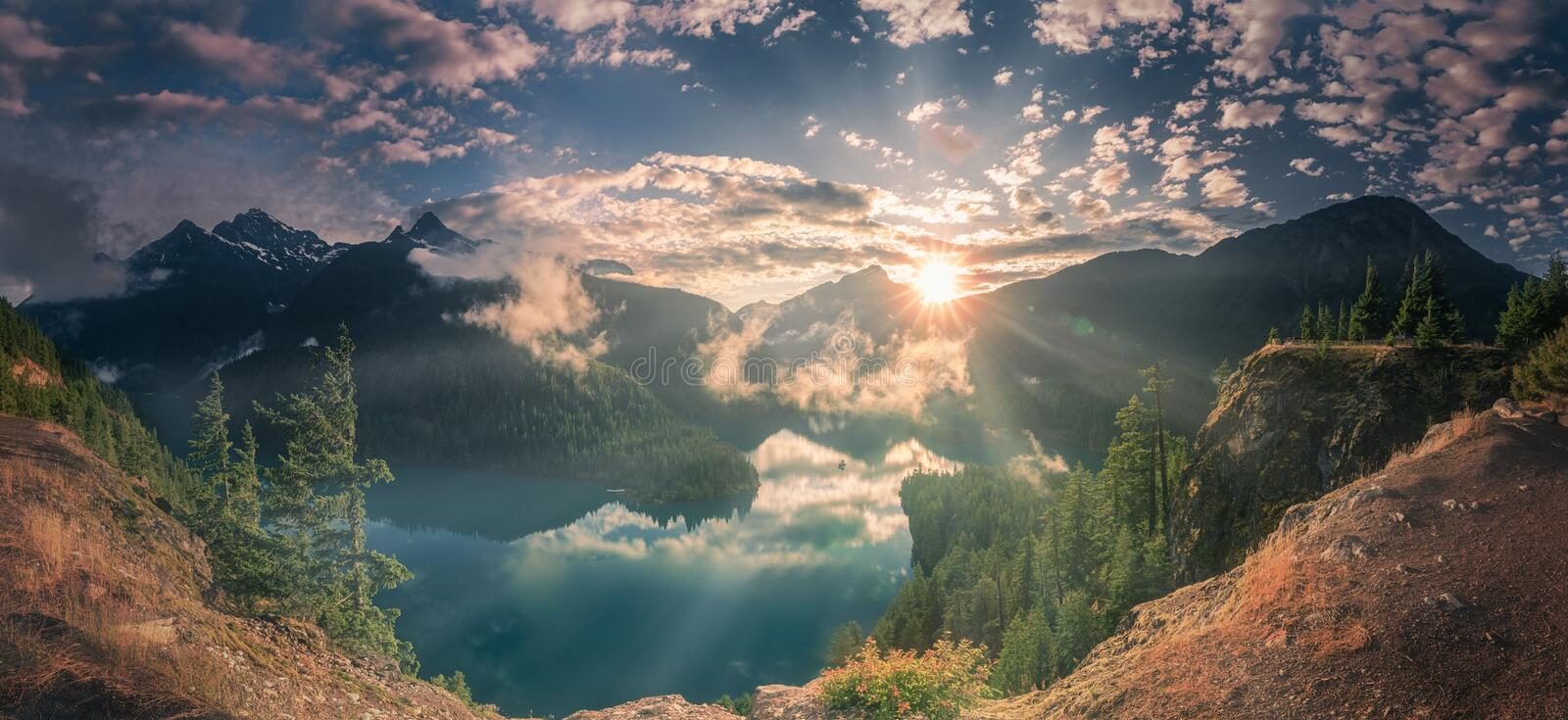Shining sunset and fog patches over lake and mountains at North Cascade National Park. Panoramic view of shining sunset and fog patches over lake and mountains royalty free stock photography