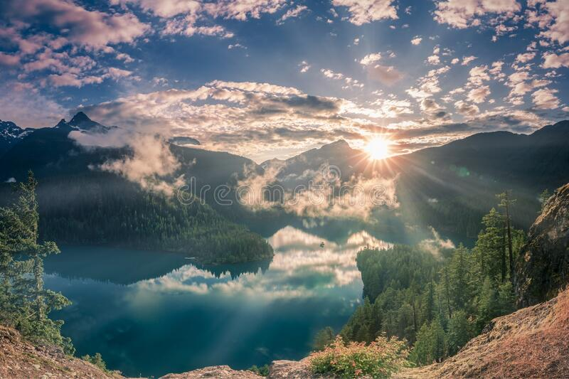Shining sunset and fog patches over lake and mountains at North Cascade National Park. In 3 to 2 aspect ratio royalty free stock image