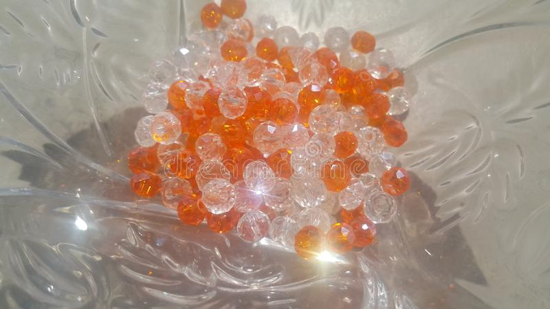 Shining, transparent, orange color crystal beads or gemstones in a glass bowl royalty free stock photography