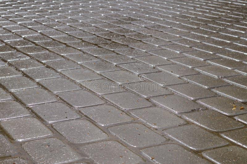 Shining wet rectangular tiled stone pavement. In diagonal layout royalty free stock photography