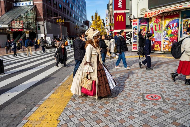 Shinjuku, Tóquio, Japão - 26 de dezembro de 2018: Menina bonita com o terno crossplay que waling nos povos dos pedestres da multi imagem de stock