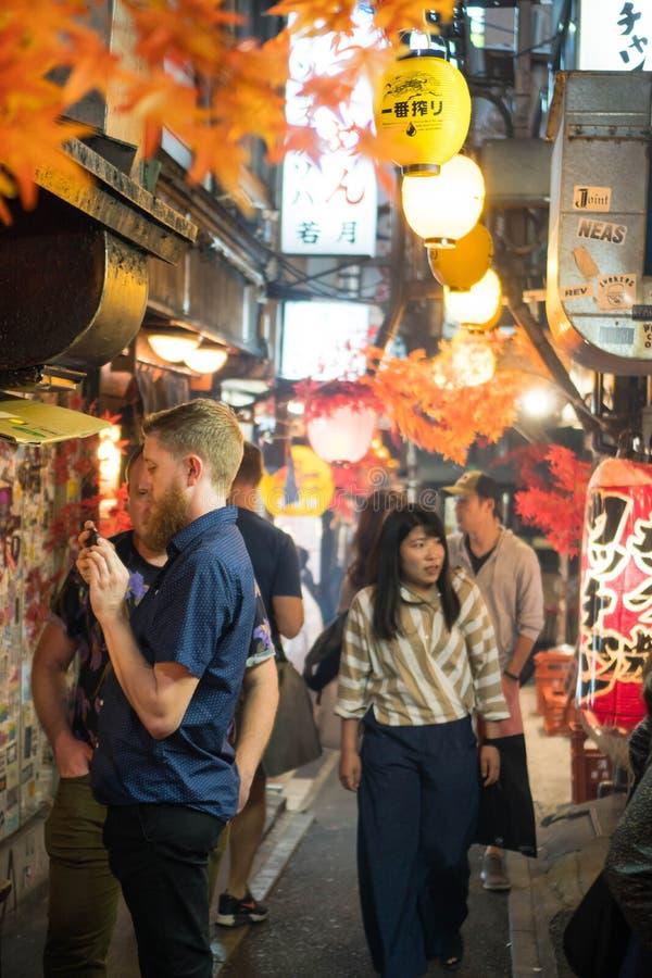 Shinjuku, Tóquio/Japão - 7 de outubro de 2018: uma rua estreita de restaurantes do alimento na vida noturna de Shinjuku fotos de stock royalty free