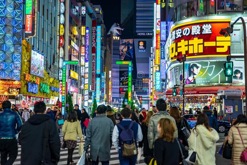 Shinjuku, Tokyo, Japan - 24. Dezember 2018: Mengenfußgängerleute, die auf Zebrastreifen an Shinjuku-Bezirk nachts in Tokyo gehen, lizenzfreie stockbilder