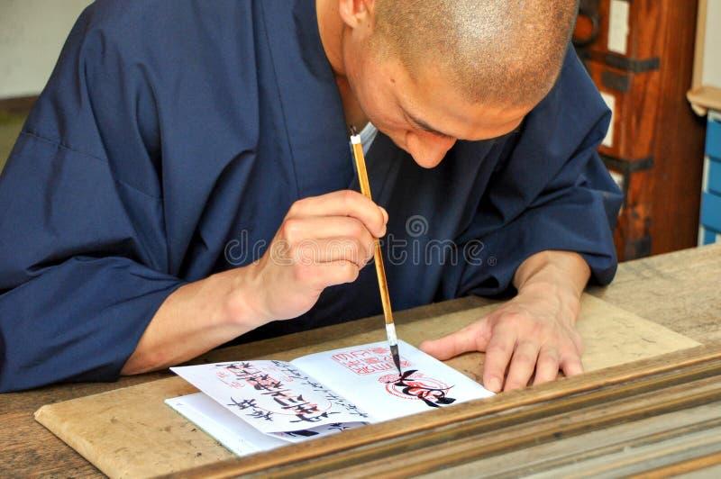 Shinshoku-Mann, der einen Shuin-Stempel für Anbetern schreibt stockfotografie