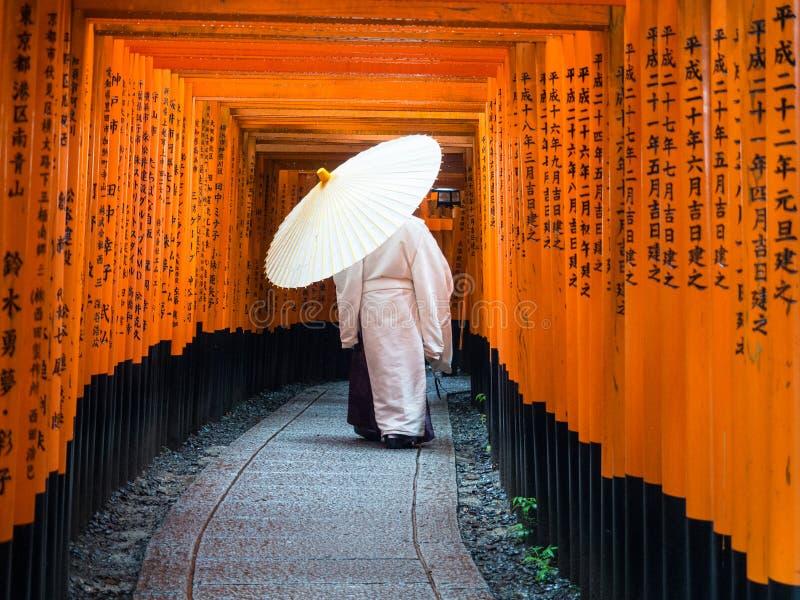 Shinto Priest in Fushimi-Inari-Taisha Shrine. A Shinto Priest resplendent in white walks through the red Torii gates of the Fushimi-Inari-Taisha shrine in Kyoto stock photography