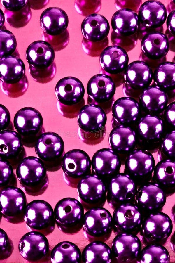 Shiny beads. Shiny mauve beads on a shiny pink background stock image