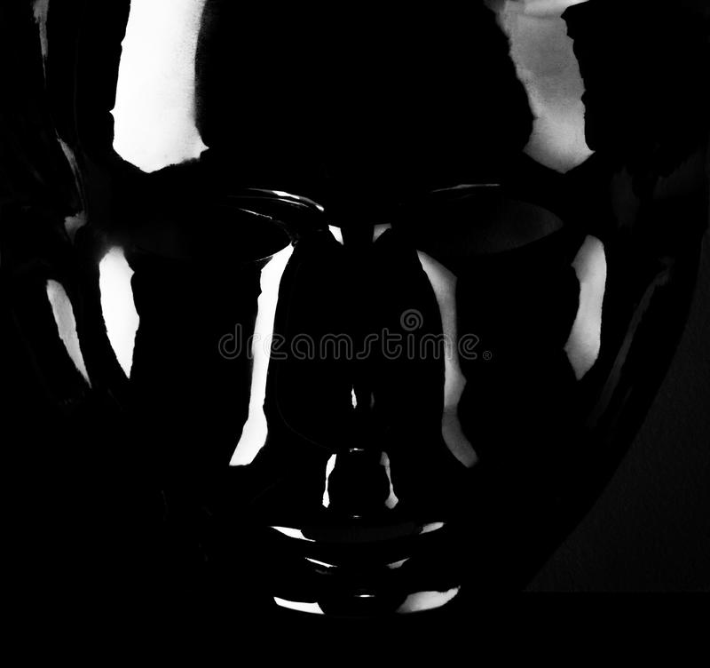 Shiny black mask silhouette on black background. Shiny black mask silhouette on pitch black background royalty free stock photos