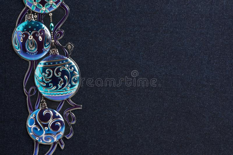 Shiny blue ball decor on dark denim background. Hanukkah or Christmas theme shiny blue and purple winter holiday ball decorations against a dark denim background stock photo