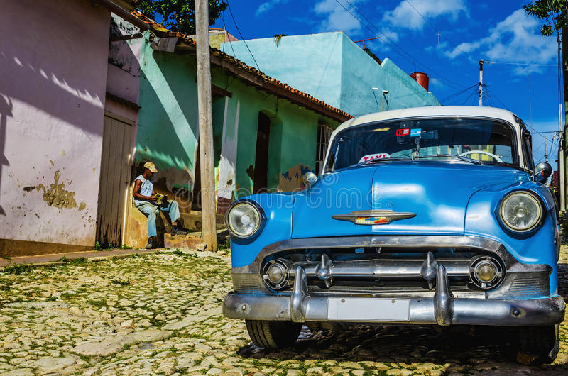 Shiny blue classic old American car and typical colorful colonial buildings in Trinidad stock photo
