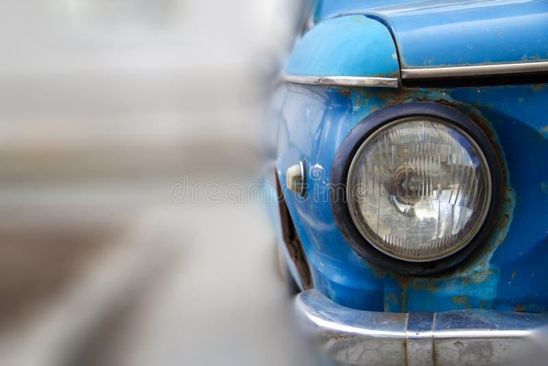 Shiny blue vintage car. Detail view of the headlight. Retro car. Front light. Retro automobile scene. Circle headlamp royalty free stock image