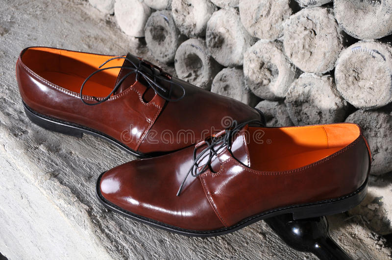 Shiny brown mens shoes, standing on interesting background. Classic shiny brown mens shoes, standing on interesting background stylized bottles royalty free stock photos