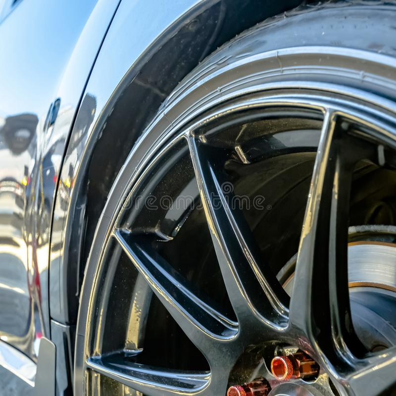 Shiny car with black mag wheel and red lug nuts stock images