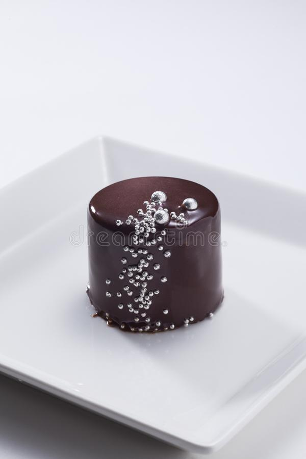 Shiny chocolate cake with silver dots royalty free stock image