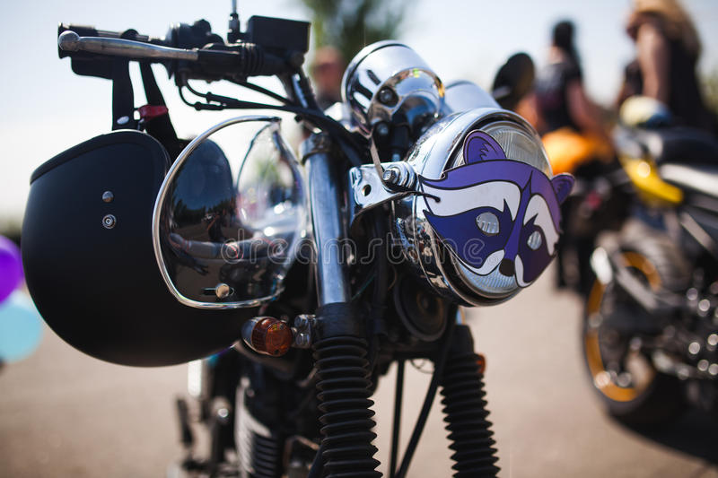 Shiny chrome caferacer motorcycle with helmet on steering bar. In Odessa royalty free stock photo