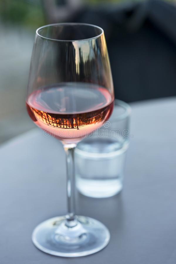 Shiny clean wine glass with pink-coloured rose wine reflecting spears of a surrounding fence standing on a gray table in a cafe. Outside and shot in the stock photos