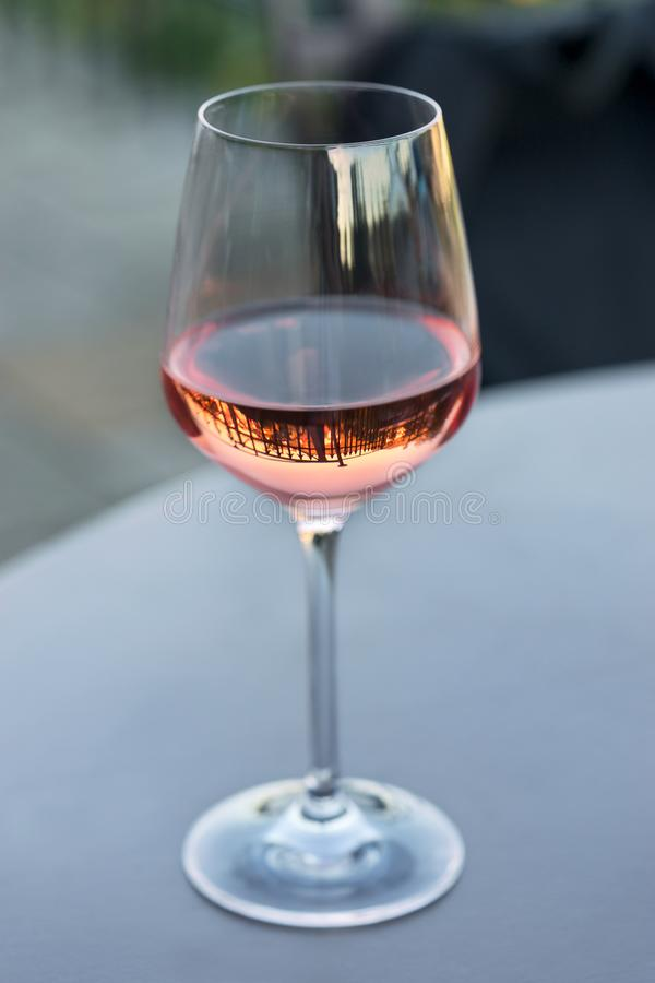 Shiny clean wine glass with pink-coloured rose wine reflecting spears of a surrounding fence standing on a gray table in a cafe. Outside and shot in the royalty free stock photos