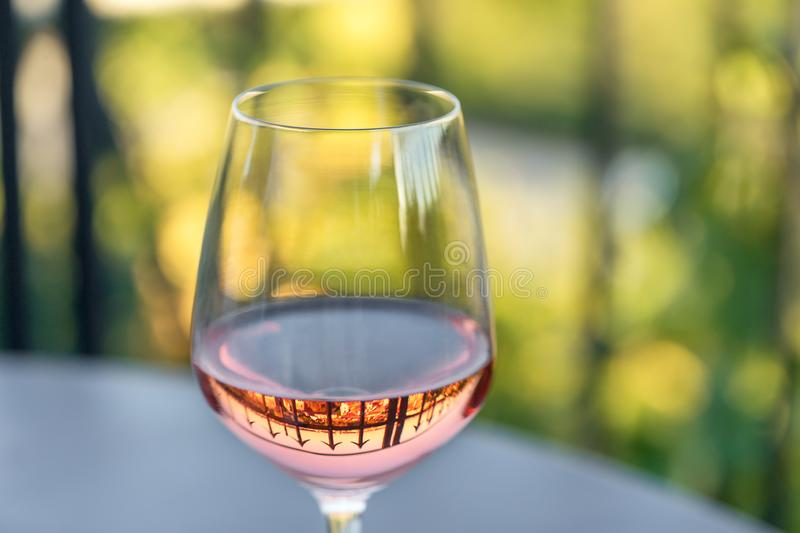 Shiny clean wine glass with pink-coloured rose wine reflecting spears of a surrounding fence standing on a gray table in a cafe. Outside and shot in the stock images