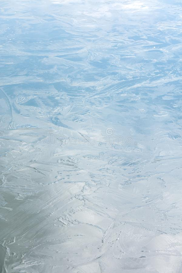 Shiny cold icy surface with sky reflections. frost patterns on ice royalty free stock photo