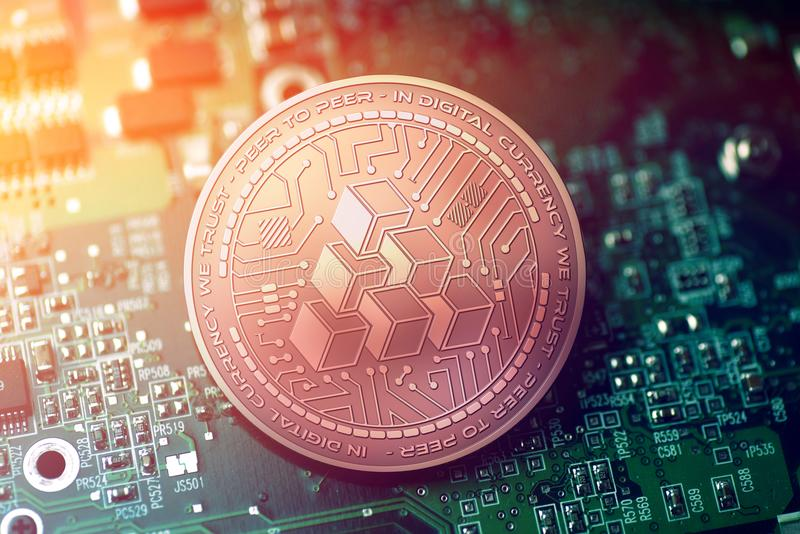 Shiny copper ATLANT cryptocurrency coin on blurry motherboard background. Token royalty free stock image