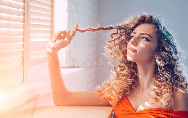 Shiny curly hair . Beautiful model woman with wavy hairstyle. Pretty woman with curly hair. royalty free stock photography