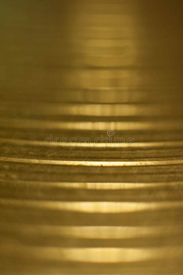 Shiny drum metal plate macro. Extreme close up of metallic drum plate, vertical image and horizontal lines on brass, selective focus royalty free stock image