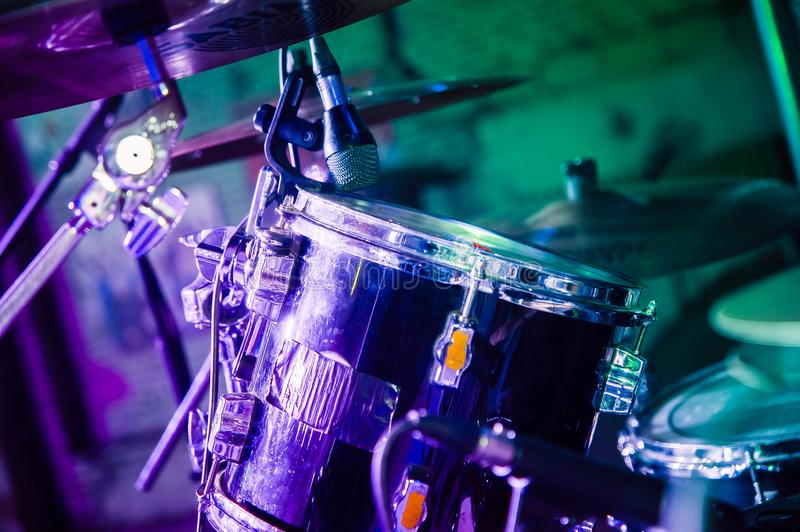 Shiny drum set on a concert stage. In purple and green light royalty free stock image