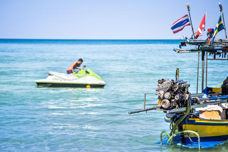 Shiny engine of motor wooden long tail boat. Jet-ski with man blurred on background. Summer vacation near the sea royalty free stock image