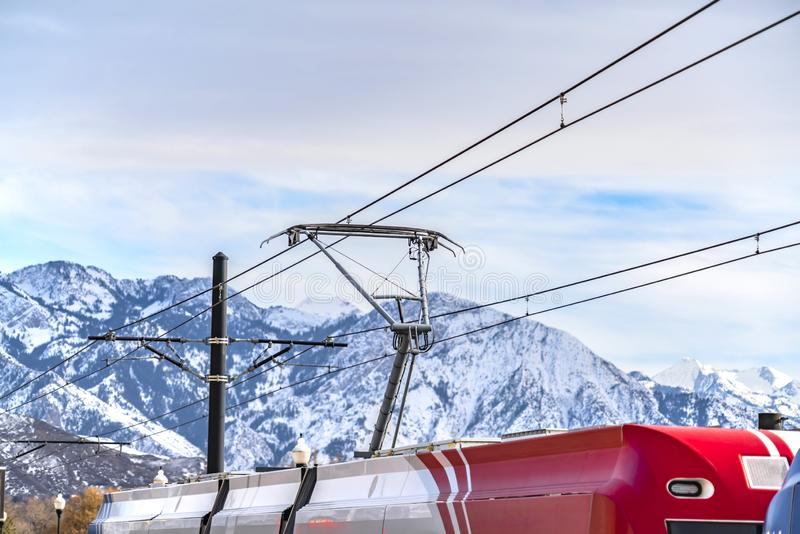 Shiny exterior of a red and white train connected to thick cable wires. A towering mountain dusted with snow under cloudy sky is in the background royalty free stock image