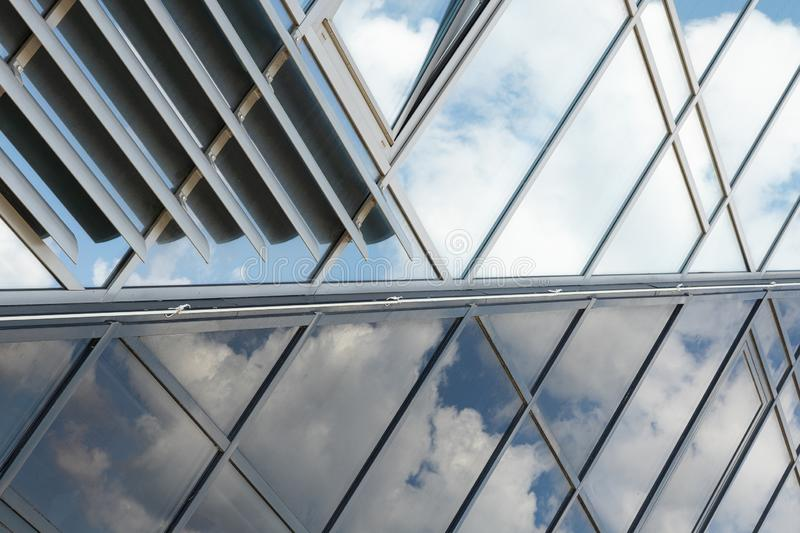 Shiny glass wall with darkening glass and sheer glass joint with sky reflection, mirrorlike stock photo