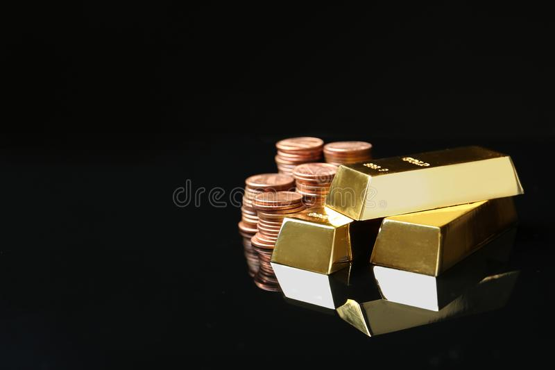 Shiny gold bars and coins on black background. Space for text royalty free stock image